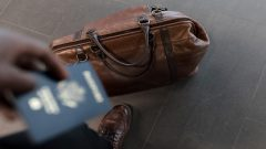 Man holding passport over weekend bag