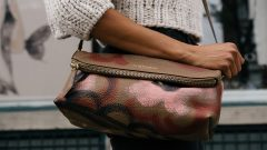 A woman carrying a leather Burberry purse