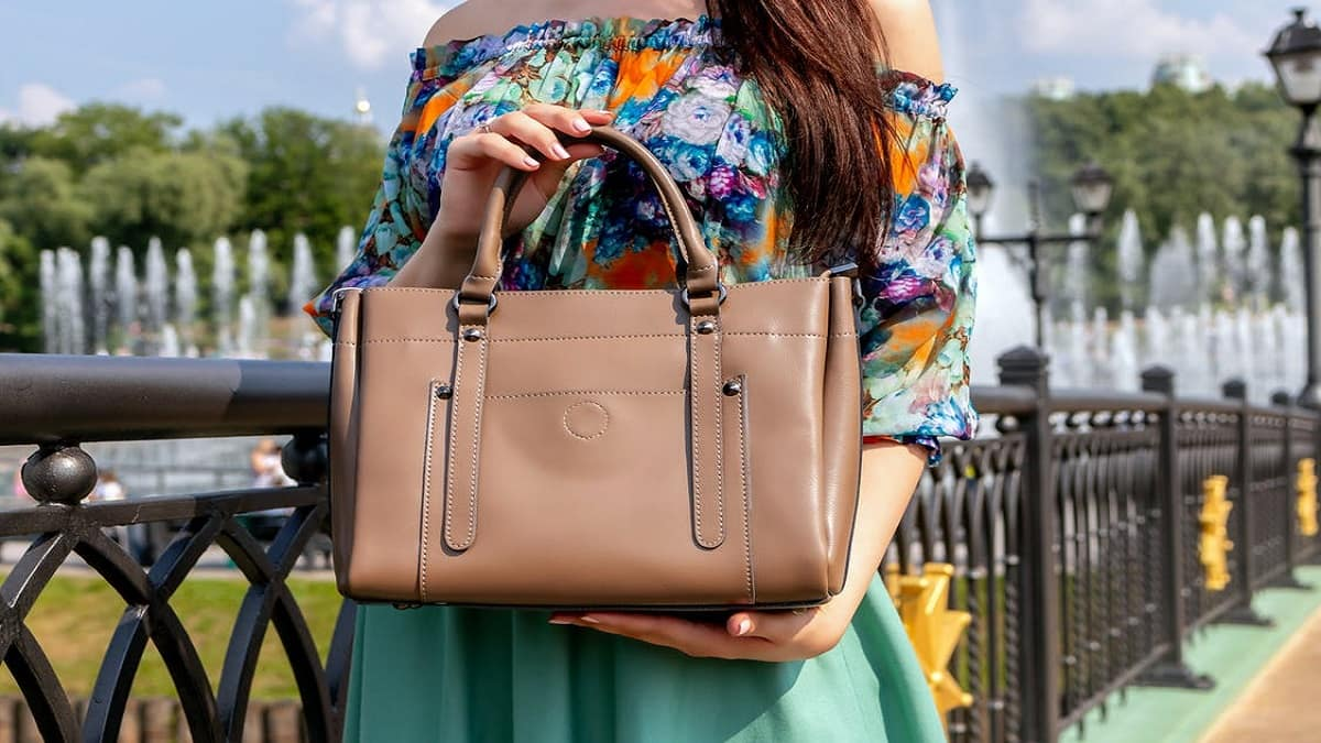 A woman holding a brown colored handbag